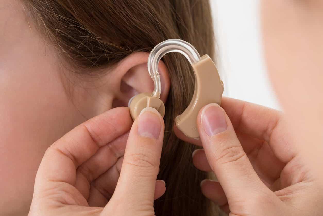 Une dame à qui le médecin insère l'appareil auditif dans l'oreille